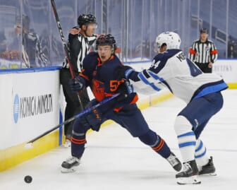 May 19, 2021; Edmonton, Alberta, CAN; Edmonton Oilers forward Kailer Yamamoto (56) tries to move the puck around Winnipeg Jets defensemen Josh Morrissey (44) during the first period in game one of the first round of the 2021 Stanley Cup Playoffs at Rogers Place. Mandatory Credit: Perry Nelson-USA TODAY Sports