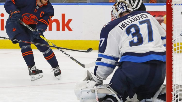 May 19, 2021; Edmonton, Alberta, CAN;Edmonton Oilers forward Connor McDavid (97) puts a shot just wide of Winnipeg Jets goaltender Connor Hellebuyck (37) during the third period in game one of the first round of the 2021 Stanley Cup Playoffs at Rogers Place. Mandatory Credit: Perry Nelson-USA TODAY Sports