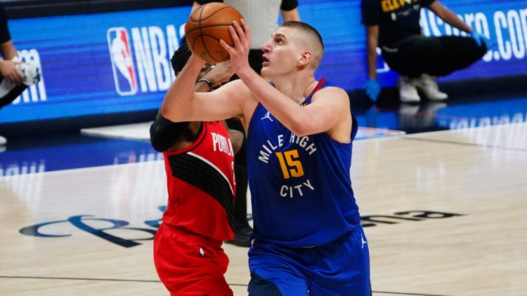 May 22, 2021; Denver, Colorado, USA; Denver Nuggets center Nikola Jokic (15) shoots the ball past Portland Trail Blazers guard CJ McCollum (3) in the second quarter during game one in the first round of the 2021 NBA Playoffs. at Ball Arena. Mandatory Credit: Ron Chenoy-USA TODAY Sports