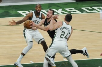 May 24, 2021; Milwaukee, Wisconsin, USA; Miami Heat guard Goran Dragic (7) drives to the basket between Milwaukee Bucks forward Khris Middleton (22) and guard Pat Connaughton (24) in the second quarter during game two in the first round of the 2021 NBA Playoffs at Fiserv Forum. Mandatory Credit: Michael McLoone-USA TODAY Sports