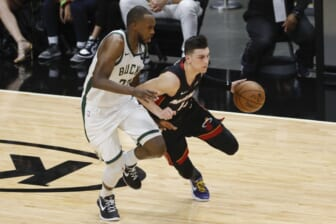 May 29, 2021; Miami, Florida, USA; Miami Heat guard Tyler Herro (14) dribbles the basketball around Milwaukee Bucks forward Khris Middleton (22) during the second quarter of game four in the first round of the 2021 NBA Playoffs at American Airlines Arena. Mandatory Credit: Sam Navarro-USA TODAY Sports