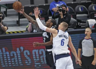 May 30, 2021; Dallas, Texas, USA; LA Clippers forward Kawhi Leonard (2) shoots past Dallas Mavericks center Kristaps Porzingis (6) during the first quarter in game four in the first round of the 2021 NBA Playoffs at American Airlines Center. Mandatory Credit: Kevin Jairaj-USA TODAY Sports