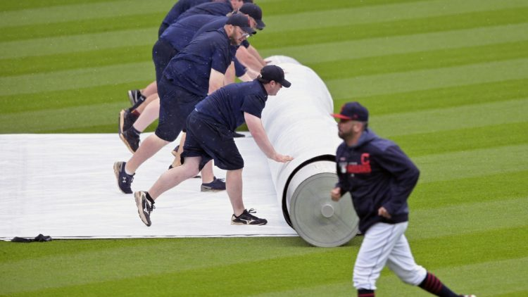 May 9, 2019; Cleveland, OH, USA; Grounds crew members roll out the tarp during a rain delay in the sixth inning of a game between the Cleveland Indians and the Chicago White Sox at Progressive Field. Mandatory Credit: David Richard-USA TODAY Sports