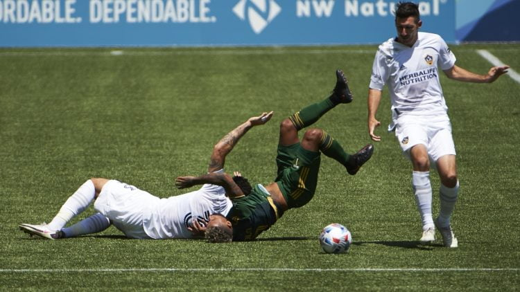 May 22, 2021; Portland, Oregon, USA; Los Angeles Galaxy defender Derrick Williams (3) slides into Portland Timbers forward Andy Polo (7) during the first half at Providence Park. Williams was issued a red card on the play. Mandatory Credit: Troy Wayrynen-USA TODAY Sports