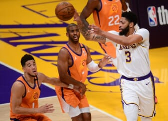 May 30, 2021; Los Angeles, California, USA; Los Angeles Lakers forward Anthony Davis (3) passes the ball against Phoenix Suns guard Chris Paul (3) and guard Devin Booker (1) during the first half in game four of the first round of the 2021 NBA Playoffs. at Staples Center. Mandatory Credit: Gary A. Vasquez-USA TODAY Sports