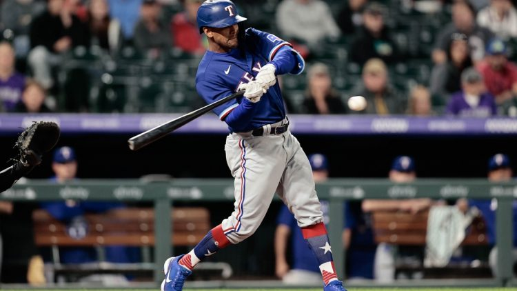 Jun 1, 2021; Denver, Colorado, USA; Texas Rangers pinch hitter Khris Davis (4) hits a solo home run in the eighth inning against the Colorado Rockies at Coors Field. Mandatory Credit: Isaiah J. Downing-USA TODAY Sports
