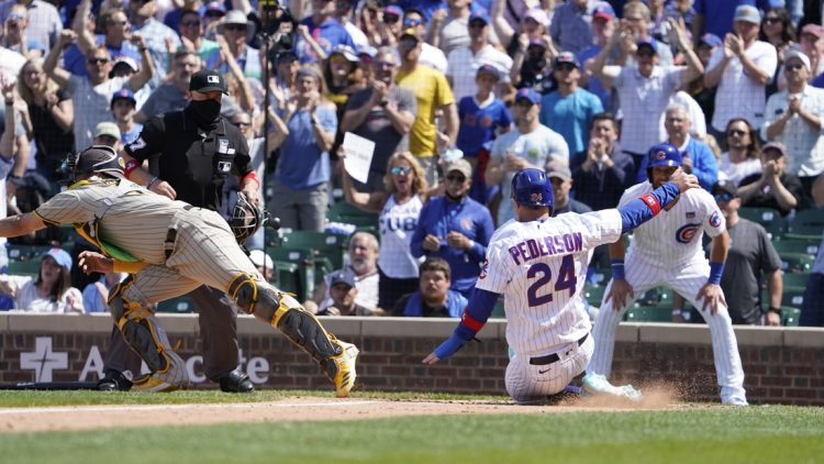 Jun 2, 2021; Chicago, Illinois, USA; Chicago Cubs left fielder Joc Pederson (24 scores as San Diego Padres catcher Webster Rivas (48) takes a late throw during the fifth inning )at Wrigley Field. Mandatory Credit: David Banks-USA TODAY Sports