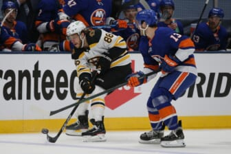Jun 3, 2021; Uniondale, New York, USA; Boston Bruins right wing David Pastrnak (88) plays the puck against New York Islanders center Mathew Barzal (13) during the first period of game three of the second round of the 2021 Stanley Cup Playoffs at Nassau Veterans Memorial Coliseum. Mandatory Credit: Brad Penner-USA TODAY Sports