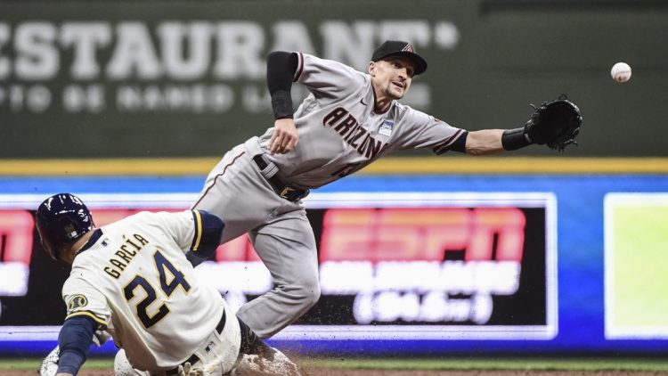 Jun 3, 2021; Milwaukee, Wisconsin, USA;  Arizona Diamondbacks shortstop Nick Ahmed (13) reaches for ball on a throwing error by first baseman Christian Walker (not pictured) as Milwaukee Brewers center fielder Avisail Garcia (24) slides advances in the fifth inning at American Family Field. Mandatory Credit: Benny Sieu-USA TODAY Sports