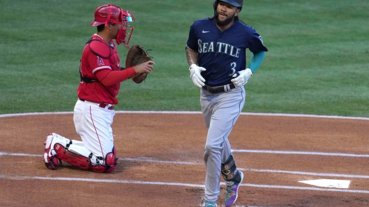 Jun 4, 2021; Anaheim, California, USA; Seattle Mariners shortstop J.P. Crawford (3) crosses home plate after hitting a solo home run in the first inning as Los Angeles Angels catcher Kurt Suzuki (24) watches at Angel Stadium. Mandatory Credit: Kirby Lee-USA TODAY Sports