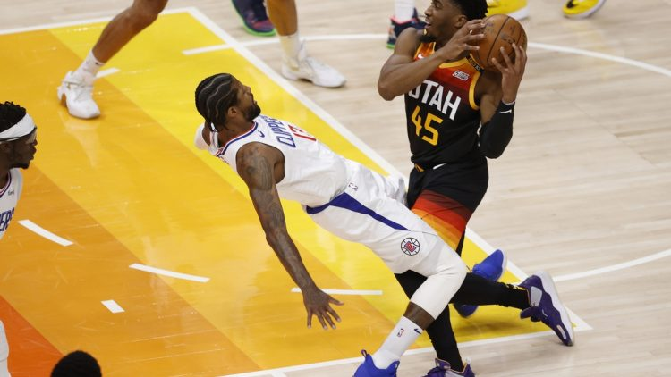 Jun 8, 2021; Salt Lake City, Utah, USA; Utah Jazz guard Donovan Mitchell (45) drives into LA Clippers guard Paul George (13) drawing the foul in the first quarter during game one in the second round of the 2021 NBA Playoffs. at Vivint Arena. Mandatory Credit: Jeffrey Swinger-USA TODAY Sports