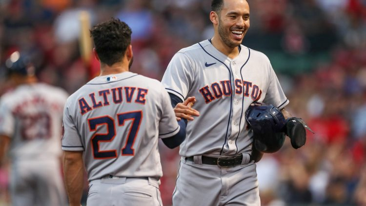 Jun 9, 2021; Boston, Massachusetts, USA; Houston Astros shortstop Carlos Correa (1) and second baseman Jose Altuve (27) react after Correa scored during the third inning against the Boston Red Sox at Fenway Park. Mandatory Credit: Paul Rutherford-USA TODAY Sports
