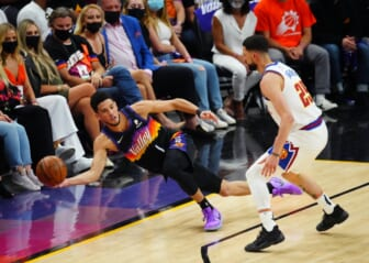 Jun 9, 2021; Phoenix, Arizona, USA; Phoenix Suns guard Devin Booker (1) passes the ball as he dives to save it from going out of bounds against Denver Nuggets guard Austin Rivers in the first half during game two in the second round of the 2021 NBA Playoffs at Phoenix Suns Arena. Mandatory Credit: Mark J. Rebilas-USA TODAY Sports