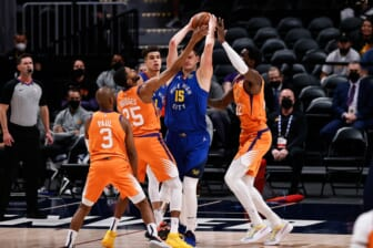 Jun 11, 2021; Denver, Colorado, USA; Denver Nuggets center Nikola Jokic (15) is defended by Phoenix Suns center Deandre Ayton (22) and forward Mikal Bridges (25) as guard Chris Paul (3) and forward Michael Porter Jr. (1) look on in the first quarter during game three in the second round of the 2021 NBA Playoffs at Ball Arena. Mandatory Credit: Isaiah J. Downing-USA TODAY Sports