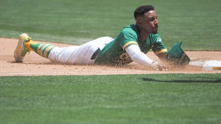 Jun 16, 2021; Oakland, California, USA; Oakland Athletics second baseman Tony Kemp (5) slides to third base against the Los Angeles Angels during the fifth inning at RingCentral Coliseum. Mandatory Credit: Kelley L Cox-USA TODAY Sports