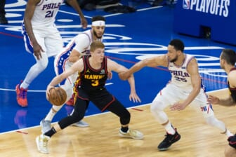 Jun 20, 2021; Philadelphia, Pennsylvania, USA; Atlanta Hawks guard Kevin Huerter (3) controls the ball against Philadelphia 76ers guard Ben Simmons (25) and guard Seth Curry (31) during the second quarter of game seven of the second round of the 2021 NBA Playoffs at Wells Fargo Center. Mandatory Credit: Bill Streicher-USA TODAY Sports