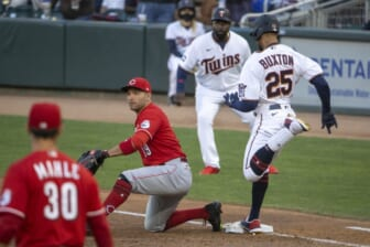 Jun 21, 2021; Minneapolis, Minnesota, USA; Minnesota Twins center fielder Byron Buxton (25) reaches first base before Cincinnati Reds first baseman Joey Votto (19) can catch the ball for a single in the second inning at Target Field. Mandatory Credit: Jesse Johnson-USA TODAY Sports