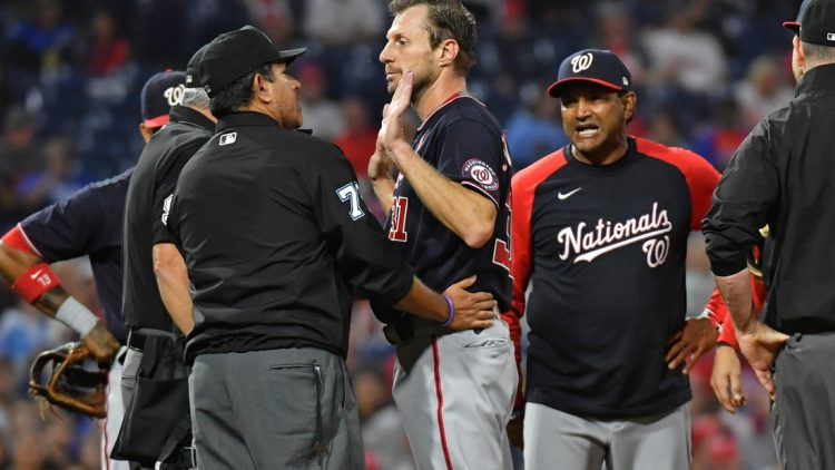 Jun 22, 2021; Philadelphia, Pennsylvania, USA; Washington Nationals  pitcher Max Scherzer (31) and manager Dave Martinez (4) talk with umpire Alfonso Marquez (72) as they check for a foreign substance on Scherzer during the middle of the fourth inning against the Philadelphia Phillies at Citizens Bank Park. Mandatory Credit: Eric Hartline-USA TODAY Sports