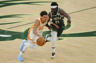 Jun 23, 2021; Milwaukee, Wisconsin, USA; Atlanta Hawks guard Trae Young (11) drives to the basket against Milwaukee Bucks guard Jrue Holiday (21) in the third quarter during game one of the Eastern Conference Finals for the 2021 NBA Playoffs at Fiserv Forum. Mandatory Credit: Michael McLoone-USA TODAY Sports