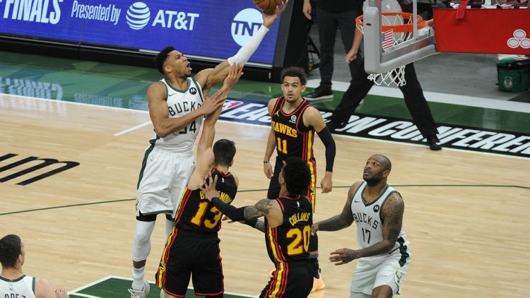 Jun 25, 2021; Milwaukee, Wisconsin, USA; Milwaukee Bucks forward Giannis Antetokounmpo (34) shoots the ball over Atlanta Hawks guard Bogdan Bogdanovic (13) in the first quarter during game two of the Eastern Conference Finals for the 2021 NBA Playoffs at Fiserv Forum. Mandatory Credit: Michael McLoone-USA TODAY Sports