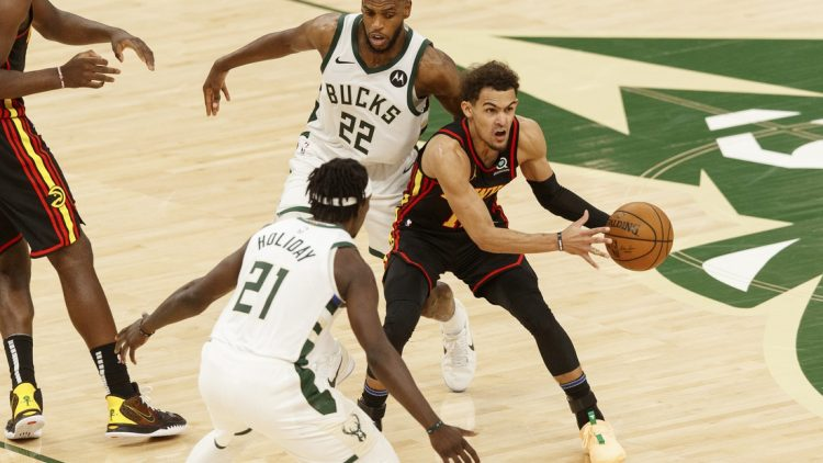 Jun 25, 2021; Milwaukee, Wisconsin, USA; Atlanta Hawks guard Trae Young (11) looks to pass the ball while defended by Milwaukee Bucks forward Khris Middleton (22) and guard Jrue Holiday (21) during the third quarter during game two of the Eastern Conference Finals for the 2021 NBA Playoffs at Fiserv Forum. Mandatory Credit: Jeff Hanisch-USA TODAY Sports