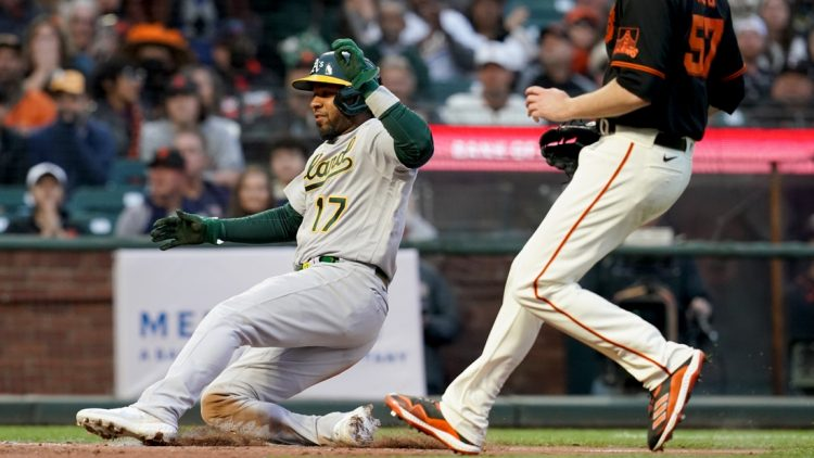 Jun 26, 2021; San Francisco, California, USA; Oakland Athletics shortstop Elvis Andrus (17) scores a run on a wild pitch against the San Francisco Giants in the third inning at Oracle Park. Mandatory Credit: Cary Edmondson-USA TODAY Sports