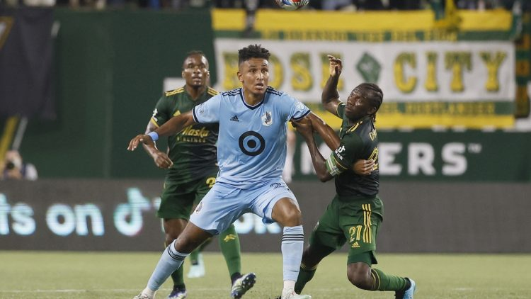 Jun 26, 2021; Portland, Oregon, USA; Minnesota United forward Juan Agudelo (21) and Portland Timbers midfielder Diego Chara (21) battle for the ball during the second half at Providence Park. Mandatory Credit: Soobum Im-USA TODAY Sports