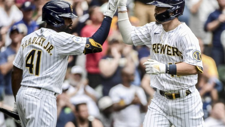 Jun 27, 2021; Milwaukee, Wisconsin, USA; Milwaukee Brewers first baseman Keston Hiura (18) is greeted by center fielder Jackie Bradley Jr. (41) after hitting a solo home run in the third inning against the Colorado Rockies at American Family Field. Mandatory Credit: Benny Sieu-USA TODAY Sports