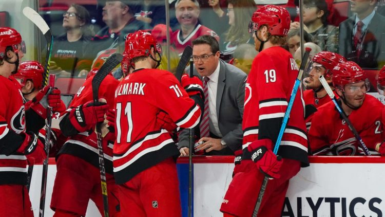 Apr 4, 2019; Raleigh, NC, USA;  Carolina Hurricanes assistant coach Dean Chynoweth talks to center Lucas Wallmark (71) and  defenseman Dougie Hamilton (19) during a time out against the New Jersey Devils at PNC Arena. The Carolina Hurricanes defeated the New Jersey Devils 3-1. Mandatory Credit: James Guillory-USA TODAY Sports