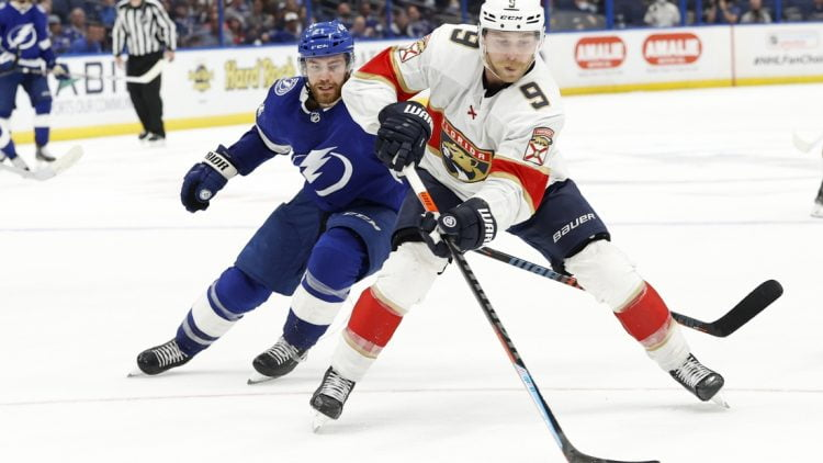 May 26, 2021; Tampa, Florida, USA; Florida Panthers forward Sam Bennett (9) skates with the puck as Tampa Bay Lightning center Brayden Point (21) defends during the third period during game six of the first round of the 2021 Stanley Cup Playoffs at Amalie Arena. Mandatory Credit: Kim Klement-USA TODAY Sports
