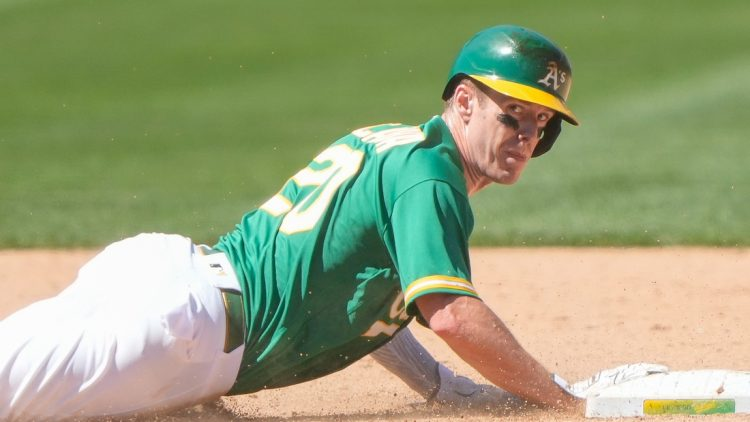 Jun 13, 2021; Oakland, California, USA;  Oakland Athletics left fielder Mark Canha (20) slides back towards second base during the sixth inning against the Kansas City Royals at RingCentral Coliseum. Mandatory Credit: Stan Szeto-USA TODAY Sports