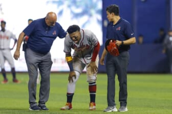 Jul 10, 2021; Miami, Florida, USA; Atlanta Braves right fielder Ronald Acuna Jr. (13) reacts as he gets check on by training staff after an apparent leg injury during the fifth inning  against the Miami Marlins at loanDepot Park. Mandatory Credit: Sam Navarro-USA TODAY Sports