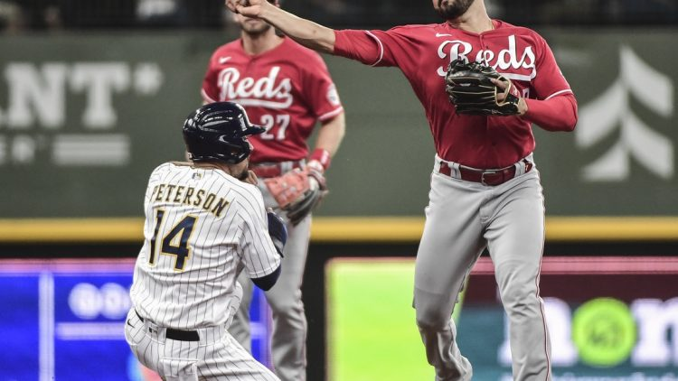 Jul 11, 2021; Milwaukee, Wisconsin, USA; Milwaukee Brewers second baseman Jace Peterson (14) breaks up a double play attempt by Cincinnati Reds third baseman Eugenio Suarez (7) in the second inning at American Family Field. Mandatory Credit: Benny Sieu-USA TODAY Sports