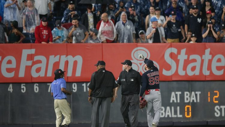 Jul 17, 2021; Bronx, New York, USA; Boston Red Sox left fielder Alex Verdugo (99) points out to second base umpire Mike Estabrook (83) and third base umpire Laz Diaz (63) a fan who threw an object at him to during the sixth inning against the New York Yankees at Yankee Stadium. Mandatory Credit: Brad Penner-USA TODAY Sports