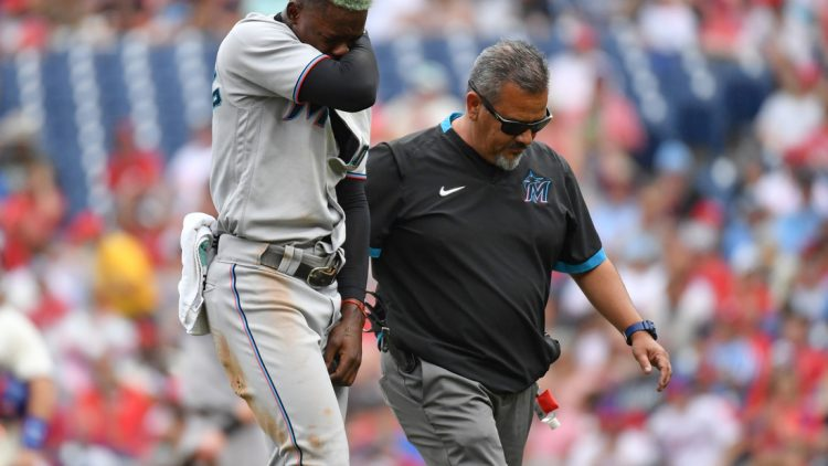 Jul 18, 2021; Philadelphia, Pennsylvania, USA; Miami Marlins second baseman Jazz Chisholm Jr. (2) walks off the field with the trainer after injuring his shoulder during the first inning against the Philadelphia Phillies at Citizens Bank Park. Mandatory Credit: Eric Hartline-USA TODAY Sports