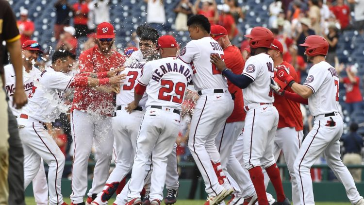 Jul 18, 2021; Washington, District of Columbia, USA; Washington Nationals shortstop Alcides Escobar (3) is mobbed by teammates after hitting a walk off RBI single against the San Diego Padres during the ninth inning at Nationals Park. Mandatory Credit: Brad Mills-USA TODAY Sports