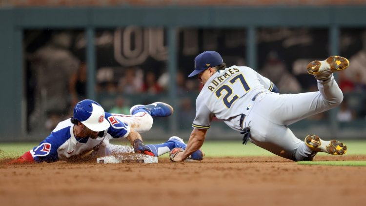 Jul 30, 2021; Atlanta, Georgia, USA; Atlanta Braves shortstop Dansby Swanson (7) steals second base ahead of the tag by Milwaukee Brewers shortstop Willy Adames (27) during the first inning at Truist Park. Mandatory Credit: Jason Getz-USA TODAY Sports