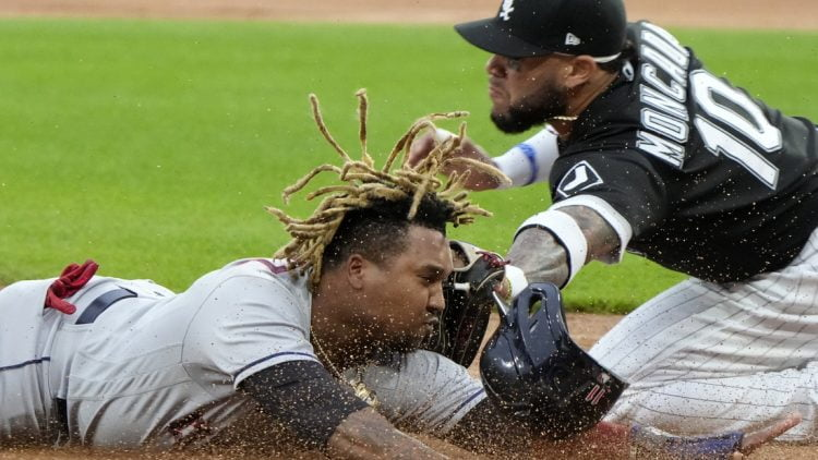 Jul 30, 2021; Chicago, Illinois, USA; Chicago White Sox third baseman Yoan Moncada (10) tags out Cleveland Indians third baseman Jose Ramirez (11) at third base during the first inning at Guaranteed Rate Field. Mandatory Credit: Mike Dinovo-USA TODAY Sports