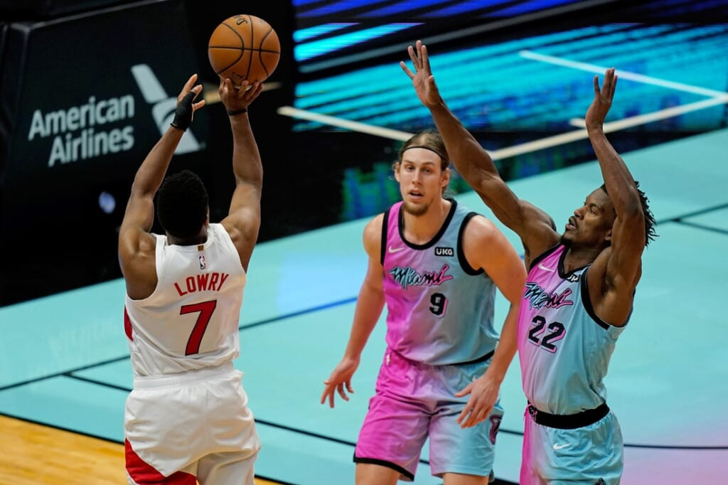 Feb 24, 2021; Miami, Florida, USA; Toronto Raptors guard Kyle Lowry (7) shoots the ball over Miami Heat forward Jimmy Butler (22) and forward Kelly Olynyk (9) during the second half at American Airlines Arena. Mandatory Credit: Jasen Vinlove-USA TODAY Sports