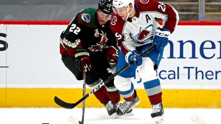 Feb 26, 2021; Glendale, Arizona, USA; Arizona Coyotes left wing Johan Larsson (22) and Colorado Avalanche defenseman Dennis Gilbert (9) go for the puck during the first period at Gila River Arena. Mandatory Credit: Mark J. Rebilas-USA TODAY Sports