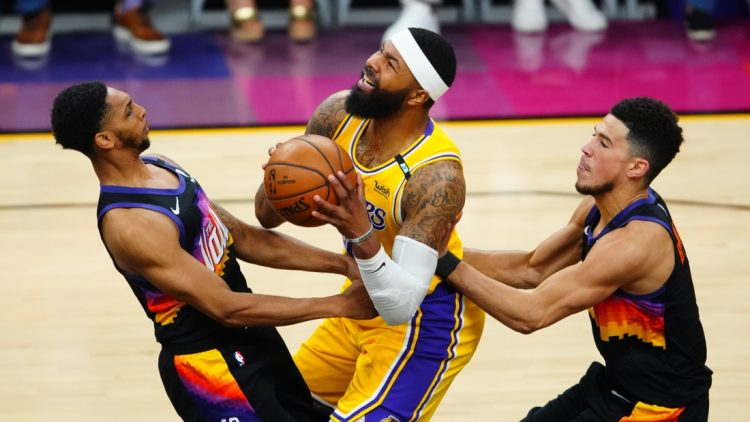 May 25, 2021; Phoenix, Arizona, USA; Los Angeles Lakers forward Markieff Morris (center) drives to the basket against Phoenix Suns guard Cameron Payne (left) and Devin Booker during game two of the first round of the 2021 NBA Playoffs at Phoenix Suns Arena. Mandatory Credit: Mark J. Rebilas-USA TODAY Sports