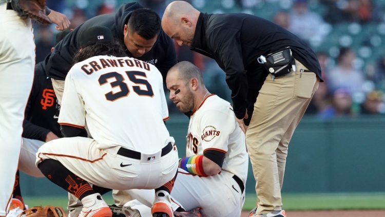 Jun 5, 2021; San Francisco, California, USA; San Francisco Giants third baseman Evan Longoria (10) is tended to by medical personnel during the ninth inning against the Chicago Cubs at Oracle Park. Mandatory Credit: Darren Yamashita-USA TODAY Sports