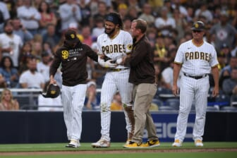 Jul 30, 2021; San Diego, California, USA; San Diego Padres shortstop Fernando Tatis Jr. (second from left) is helped off the field by manager Jayce Tingler (left) and a trainer after an injury during the first inning against the Colorado Rockies at Petco Park. Mandatory Credit: Orlando Ramirez-USA TODAY Sports
