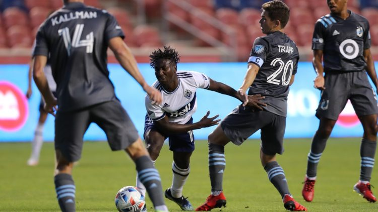 Jul 31, 2021; Sandy, Utah, USA; Vancouver Whitecaps midfielder Janio Bikel (19) and Minnesota United midfielder Will Trapp (20) play for a ball in the first half at Rio Tinto Stadium. Mandatory Credit: Rob Gray-USA TODAY Sports