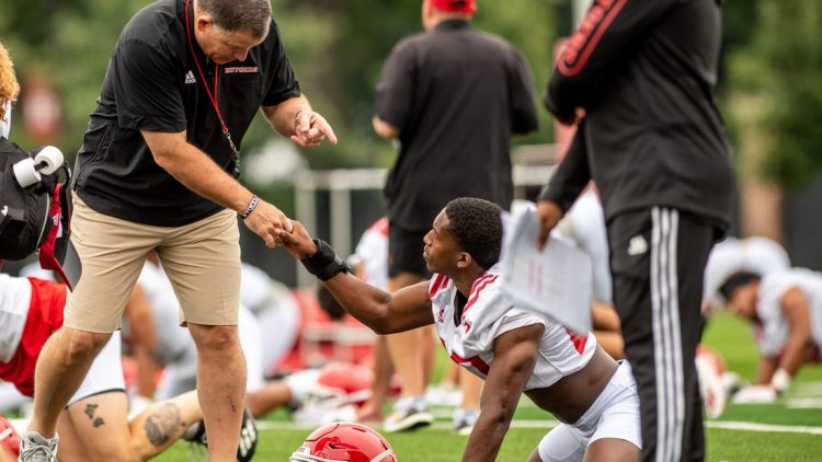Rutgers football's first practice of training camp is held In Piscataway on Wednesday August 4, 2021. Head coach Greg Schiano shakes a player's hand during practice.  Rutgers Football Training Camp Practice