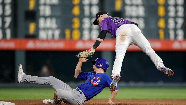 Aug 4, 2021; Denver, Colorado, USA; Chicago Cubs pinch hitter Matt Duffy (5) is tagged out by Colorado Rockies shortstop Trevor Story (27) as he attempts to steal second base in the ninth inning at Coors Field. Mandatory Credit: Isaiah J. Downing-USA TODAY Sports