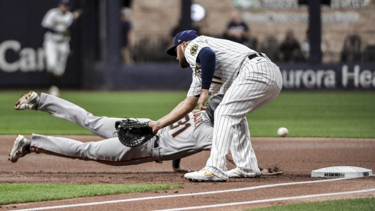 Aug 6, 2021; Milwaukee, Wisconsin, USA; Milwaukee Brewers first baseman Rowdy Tellez (11) cannot field the ball on a throwing error by pitcher Corbin Burnes (not pictured) while trying to pick off San Francisco Giants center fielder LaMonte Wade Jr (31) in the first inning at American Family Field. Mandatory Credit: Benny Sieu-USA TODAY Sports