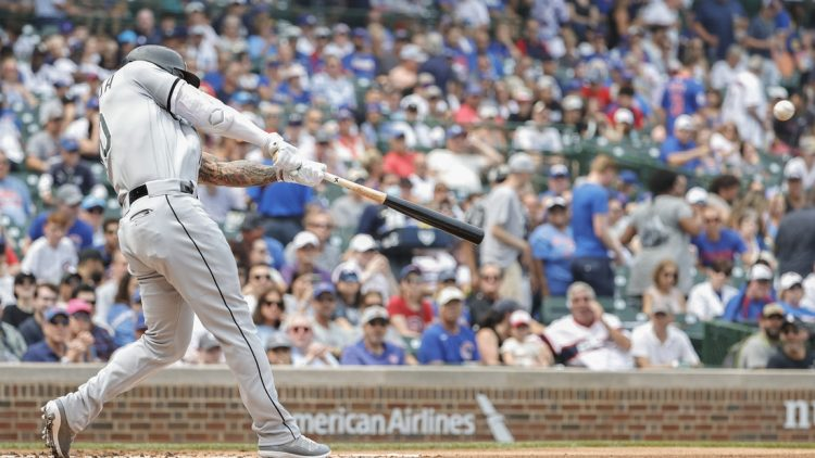 Aug 7, 2021; Chicago, Illinois, USA; Chicago White Sox third baseman Yoan Moncada (10) hits a two-run double against the Chicago Cubs during the first inning at Wrigley Field. Mandatory Credit: Kamil Krzaczynski-USA TODAY Sports