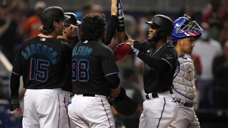 Aug 13, 2021; Miami, Florida, USA; Miami Marlins right fielder Bryan De La Cruz (77) celebrates with teammates after hitting a grand slam home run in the 2nd inning against the Chicago Cubs at loanDepot park. Mandatory Credit: Jasen Vinlove-USA TODAY Sports