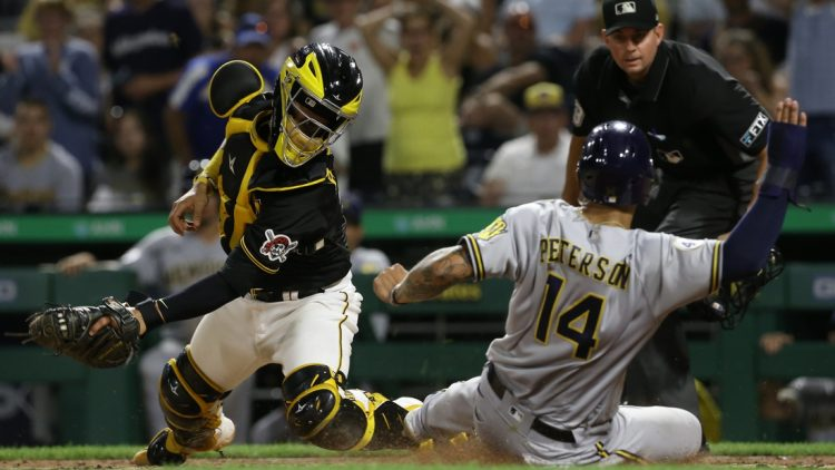 Aug 14, 2021; Pittsburgh, PA, USA; Milwaukee Brewers first baseman Jace Peterson (14) scores past Pittsburgh Pirates catcher Michael Perez (5) from second base after a throwing error by Perez on a pick-off attempt during the sixth inning at PNC Park. Mandatory Credit: Charles LeClaire-USA TODAY Sports